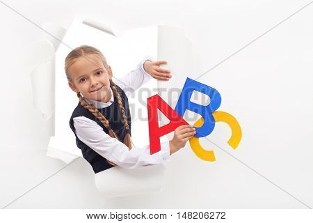 Little girl with alphabet letters and copy space leaning through hole in paper layer
