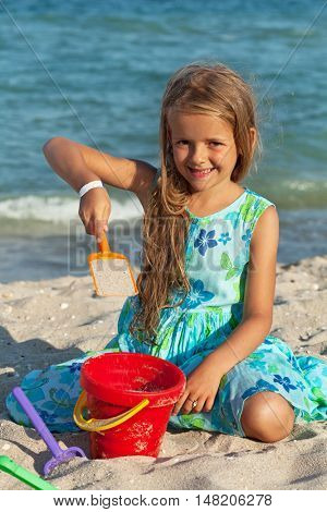 Young girl with long hair playing in the sand by the sea
