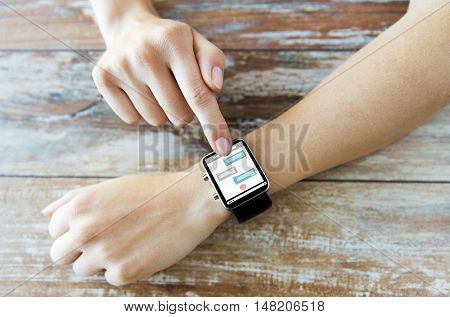 business, modern technology, social network, communication and people concept - close up of female hands setting smart watch with messenger on screen on wooden table