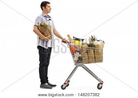 Full length portrait of a man waiting in line with a shopping cart and a paper bag isolated on white background