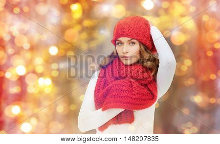 winter, people, christmas and holidays concept - woman in hat, muffler and pullover over lights background