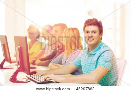 education, technology and school concept - smiling male student with classmates in computer class