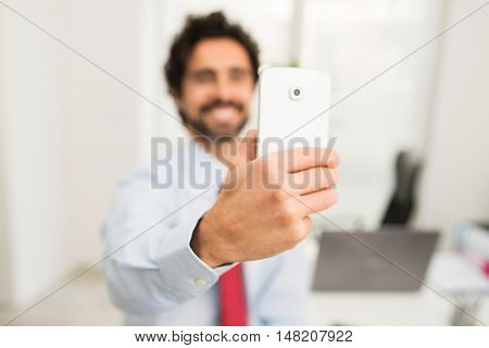 Businessman taking a selfie portrait in his office. Focus on the hand