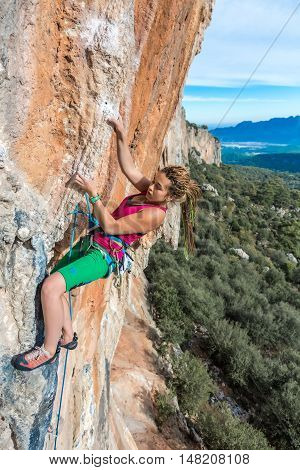 Young Female Climber ascending vertical rocky wall sporty Clothing Red Shirt Green Pants using Rope and other Safety Gear