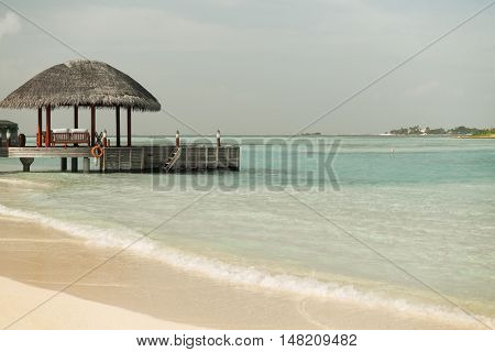 travel, tourism, vacation and summer holidays concept - access to patio or terrace with canopy on maldives beach sea shore