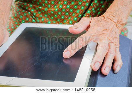 horizontal photo of closeup asian elder woman using tablet technology concept.