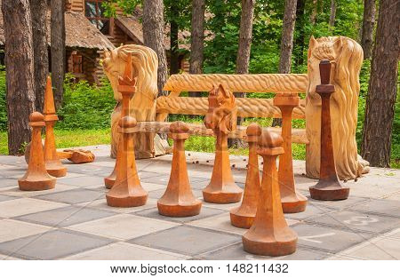 Large wooden chess in a summer forest