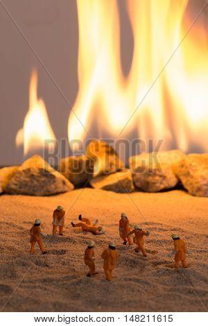 Miniature firemen at work near a real fire