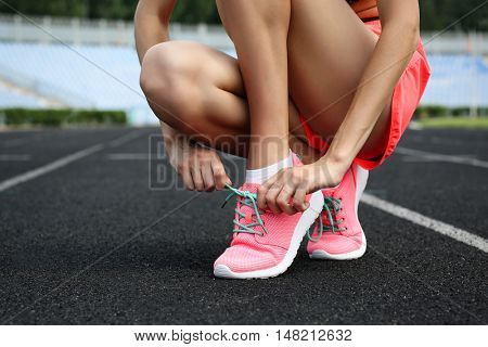 Woman tying lace on her sneakers on a running stadium