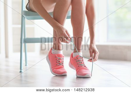 Woman tying her pink sneakers