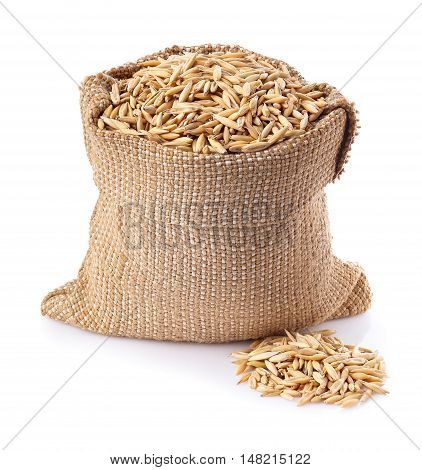 grains of oat with husk in burlap bag isolated on white background. Uncooked oat grains with husk isolated on white background. Oat grains with husk. Cereal grains