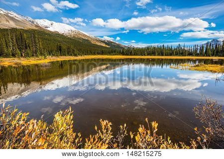 The concept of active tourism. Sky and clouds reflected in the smooth water in the lake. Rocky Mountains on a sunny day