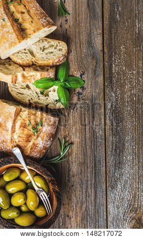 Green mediterranean olives in bowl and slices of freshly baked ciabatta over rustic wooden background. Top view, copy space, vertical composition