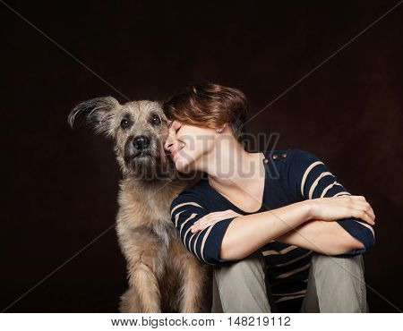 Portrait Of A Beautiful Young Woman With A Funny Shaggy Dog On A Dark Background. High Quality, Phot