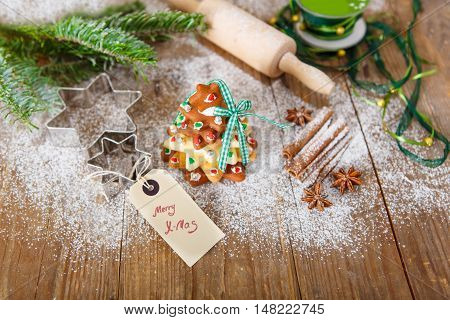 Homemade baked Christmas gingerbread tree on vintage wooden background. Anise, cinnamon, baking roll, star forms and decoration utensils. With icing sugar als snow. Selfmade gift for xmas.