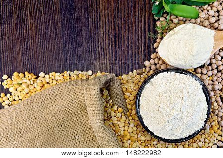 Flour chickpeas in a bowl and of pea in a spoon, green pods on burlap background on wooden board