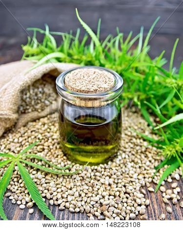Hemp oil in a glass jar with grain in a bag, cannabis leaves and stalks on a wooden boards background