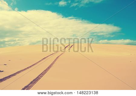 Vehicle tracks over a remote, deserted sand dune. Vintage retro tonal effect.