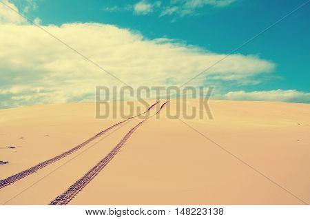 Vehicle tracks over a remote, deserted sand dune. Vintage retro tonal effect.