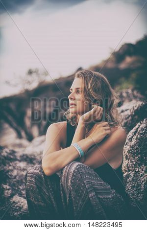 beautiful young woman sitting on the rocks at sunset background