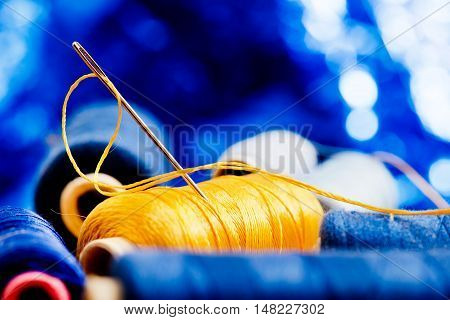 needle and yellow thread on the blue background