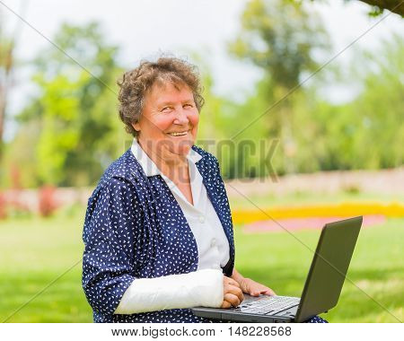 Grandmother with bandage and laptop outdoors using social network.