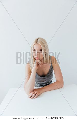 Portrait of a beautiful pensive blonde girl looking at camera isolated on the grey background