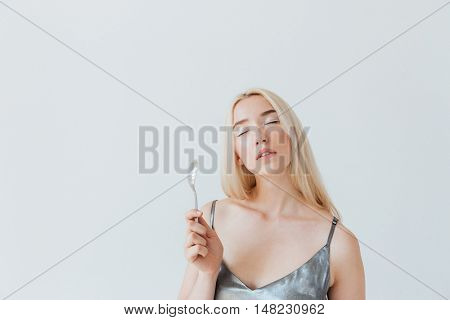 Blonde fashion glamour girl in silver shiny dress holding spoon with eyes closed isolated on the grey background