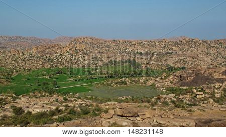 Green oasis of rice fields between granite mountains. Unique landscape in Hampi India.