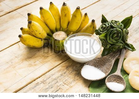 Dessert from  ripe bananas  have raw material of nature   such as coconut milk and sugar and salt on wooden background.Top view and close up.