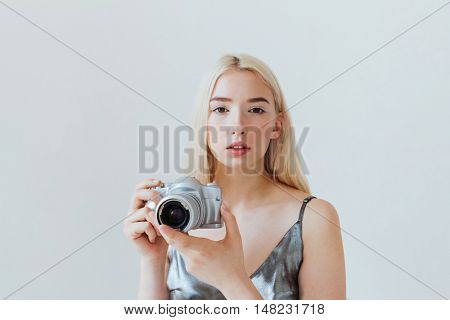 Pretty young blonde girl with photo camera sitting at the white table isolated on the grey background