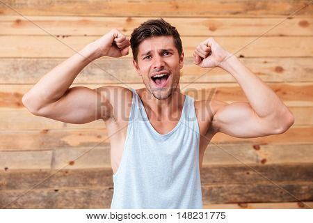 Portrait of a cheerful young fitness man celebrating victory isolated on a wooden background