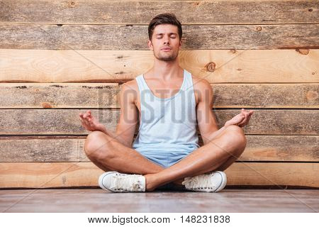 Attractive casual man sitting on the floor with legs crossed and eyes closed over wooden background