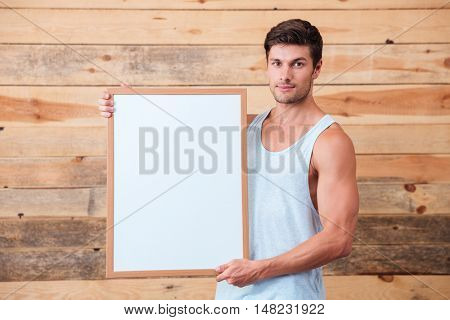 Casual happy young man holding blank board over wooden background and looking at camera
