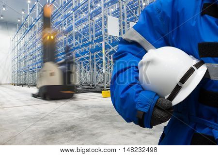 Worker in uniform with safety hardhat for dangerous accident protection in warehouse during work