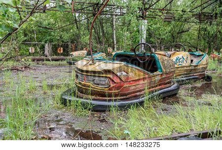 rusty cars in abandoned playground of Pripyat park, Chernobyl