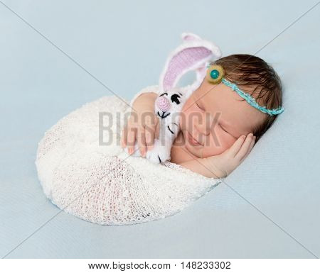 wrapped newborn baby with toy sleeping on hand, closeup