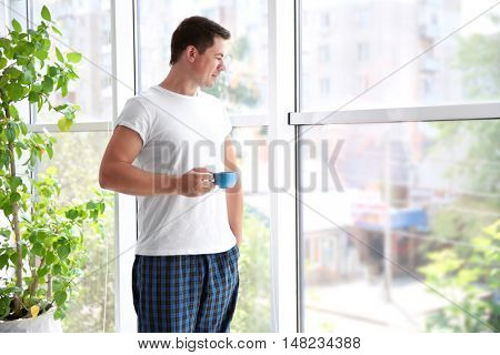 Handsome man standing near window with cup of morning coffee