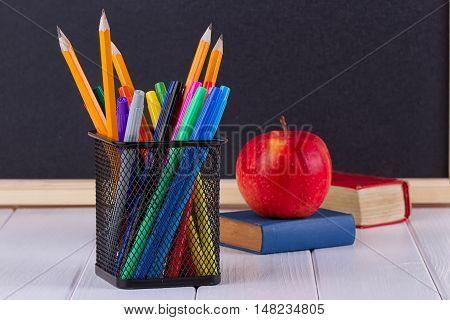 Background blackboard chalk books pencils and an apple