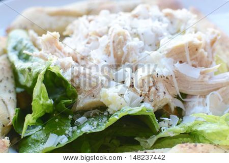 Close up view of Chicken caesar salad with parmesan shavings