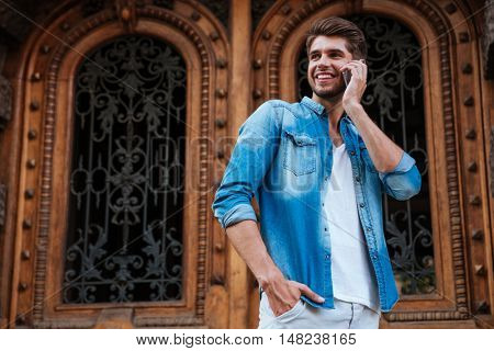 Happy smiling man talking on the mobile phone while standing infront of the wooden door on the street
