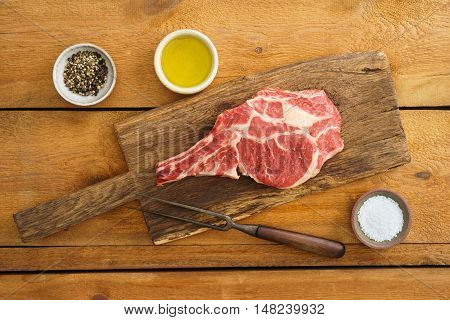 Dry aged Rib eye steak on wooden board with pepper, salt and oil
