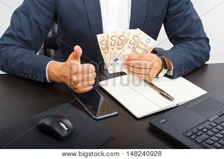 Office manager holding money in his hands