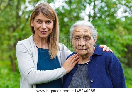 Portrait of a smiling beautiful young woman holding her tired grandmother
