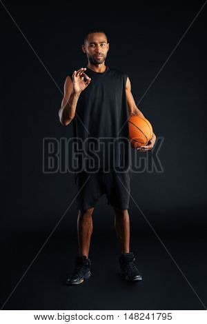 Concentrated serious african sports man holding basket ball and showing okay gesture isolated on a black background
