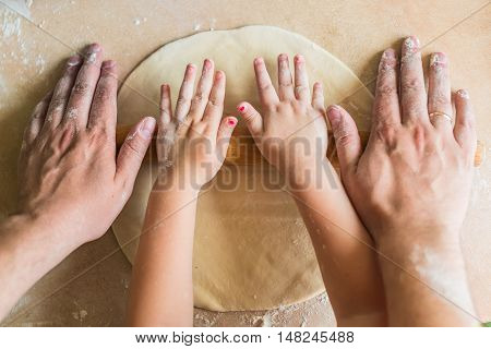 Children and dad hands rolled dough with a rolling pin on the table