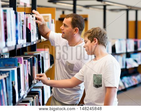 Boy and his father in library