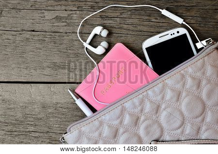 Set of female accessories looks out of the bag. Passport, pen, phone, headphones on a wooden background
