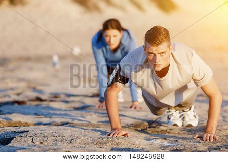 Young couple doing push ups on ocean beach