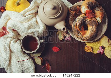 top view of cozy autumn breakfast on table in country house. Hot tea pumpkins bagels and flowers.